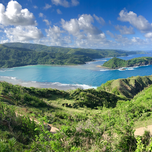 A landscape photos of a tropical bay with lush green hills.