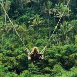 A woman on a swing overtop of a jungle