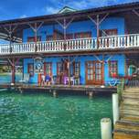 A two story building on stilts over some tropical waters.
