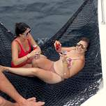 Two girls holding cans of beer laying in a netted area on a yacht.