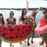 5 girls in bikinis holding giant colourful floatation devices on a yacht.