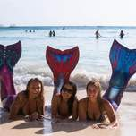 Three girls wearing mermaid outfits pose on the beach.