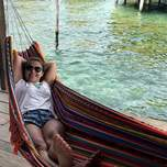 A smiling Girl laying in a hammock next to the ocean.