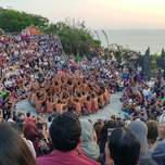 An audience of people in a small round ampitheater surround a group of Balinese men sitting in a circle.