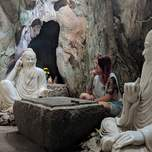 A woman poses with two vietnamese sculptures in a cave in vietnam.