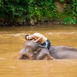 Traveler sitting on top of an elephant while giving it a bath in Thailand
