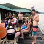 A group of people share drinks on a floating rafthouse on a lake.