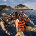 A group of young people holding drinks while floating in the sea.
