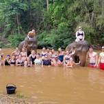 A group of travelers and two elephants pose for a group shot in a river.