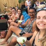 A group of young travelers sit at a beach bar drinking cocktails.