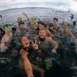 A group of travelers swimming in the water with snorkels and masks posing for a photo.