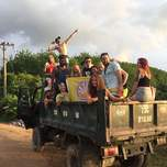 A group of travelers pose in the back of a dump truck.