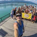 A man takes a selfie with a group of travelers in the background posing in front of a lake.