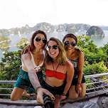 A selfie of three girls on a junk ship with green jungled islands behind them.