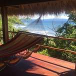 An empty hammock perched high above a beautiful view of the ocean and a beach.