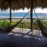 A couple of travelers laying in hammocks overlooking a beautiful bay.
