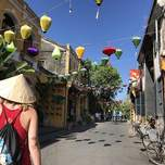 A girl wearing a Vietnamese rice hat walks down an empty street with Asian lanterns strung across it.