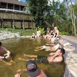 A group of travelers soak in some hot springs.