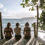 Three girls sitting on the end of a dock near the ocean in Thailand