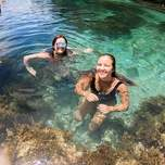 Two smilling girls floating in a lagoon.