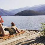 A traver writes in her journal,laying on her stomach on a deck overtop of a lake.