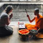 traveler being blessed by a monk at Angkor Wat in Cambodia