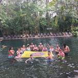 A group of people in a natural pool holding a large Free & Easy Traveler flag.