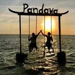 A large swing located in a shallow part of the sea.  Two girls on it in front of a sunset.