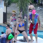 A group of young people dance and drink next to a pool