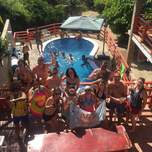 A group of young adults pose above a pool while some people swim and drink and party.