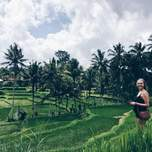 A girl poses in some lush green rice terraces.