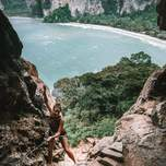 A girl is rappelling down the side of a cliff with a beautiful beach behind her.