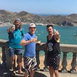 Three young men holding beers at a viewpoint overlooking San Juan del Sur.