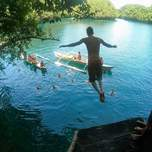 A man is seen from behind jumping off of a platform into a beautiful tropical sea.