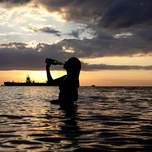 A woman is drinking a beer in the ocean while the sunsets.