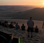 Group of travelers enjoying the sunset in Huacachina Desert in Peru