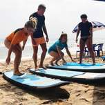 A group of travelers learning to surf.