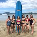 A group of young women pose in front of a surfboard on a beach.
