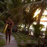 A girl in a bikini walking with a surfboard as the sun sets in the background.