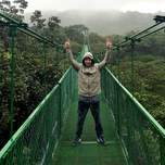 A young man stands on a suspension bridge above a rainforest.