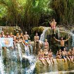 Group of travelers sitting in a waterfall in Laos