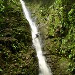 A man holds onto a rope as he rappels down a waterfall.