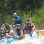A group of people intensely white water rafting.