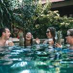 A group of travelers sipping cocktails in a pool.