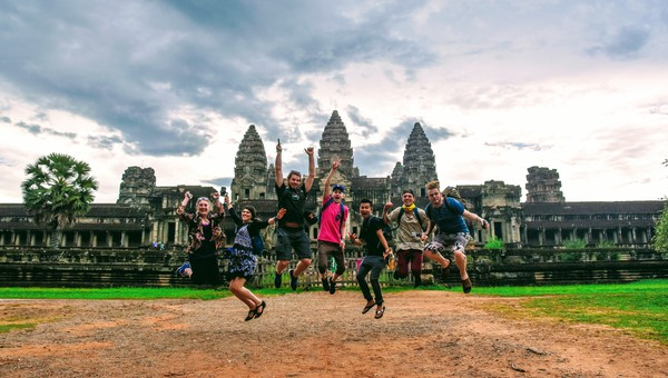 A group of travelers jumping with joy in front of Angkor Wat.