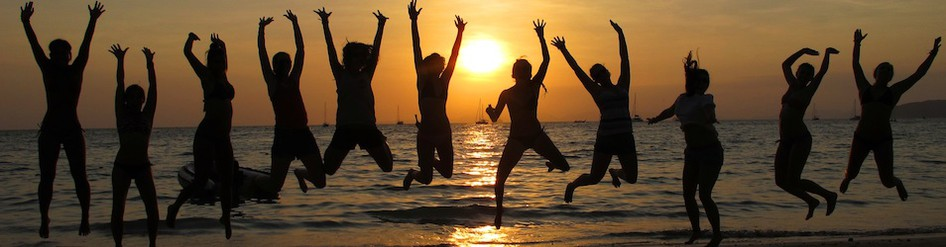 group of travelers jumping on a beach as the sun sets