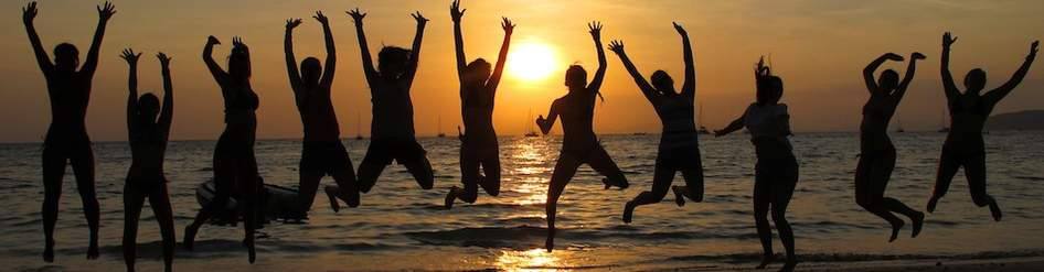 a group of happy people jumping holding hands in front of a beach