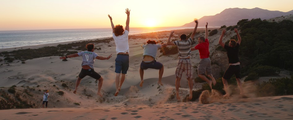 A group of travelers jumping as the sun sets over the ocean