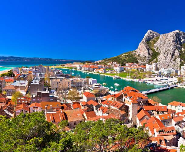 An aerial shot of the town of omis with a looming mountain in the background