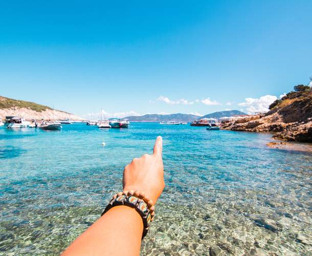 A hand stretches out pointing a clear water bay.